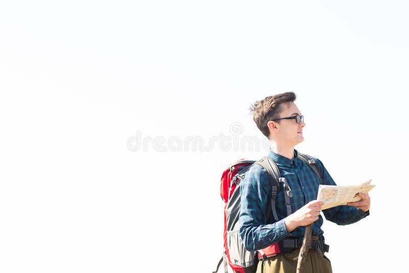 Viajero joven con la mochila que mira el mapa para las direcciones mientras que camina en el campo imagenes de archivo
