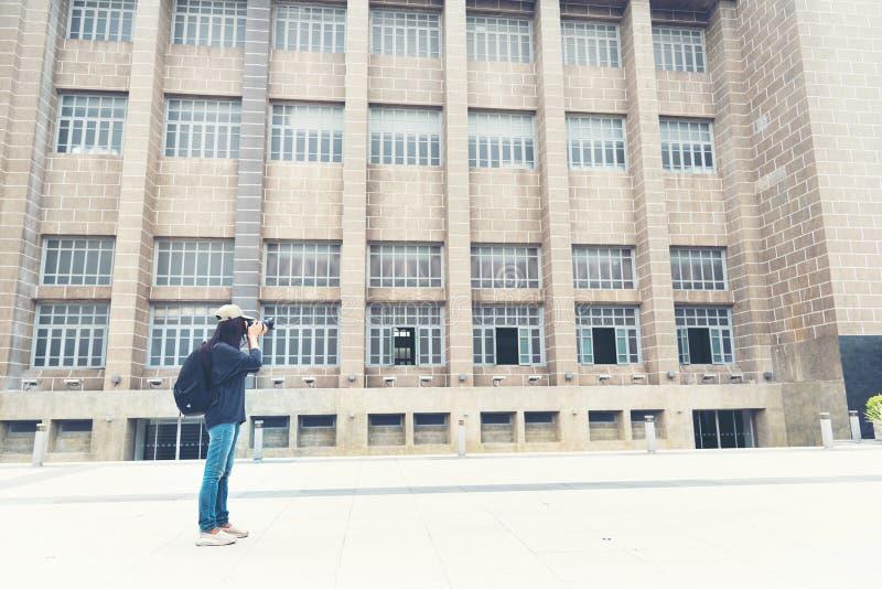 Viajero joven femenino con la mochila y photocamera en la ciudad vieja Mochila hermosa de la mujer alrededor de la palabra imagen de archivo libre de regalías