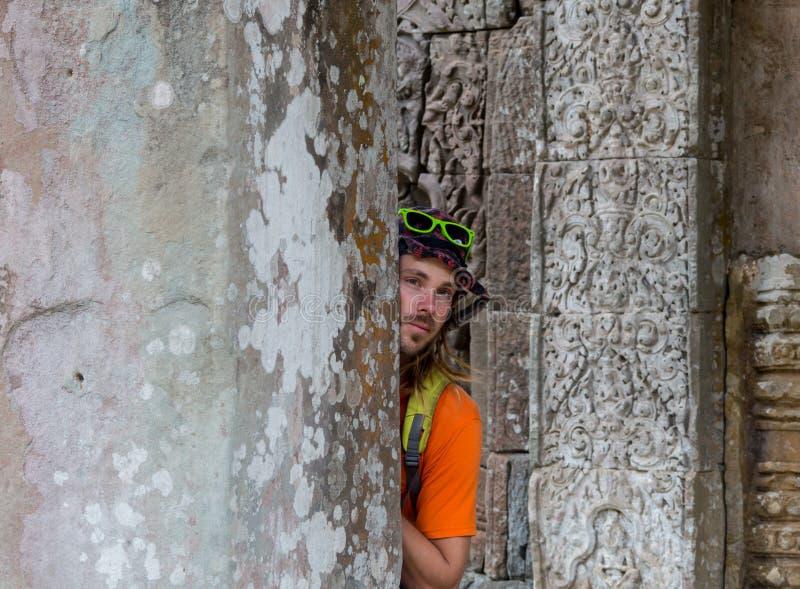 Viajero joven que lleva un sombrero con la mochila y el trípode - en Angkor Wat imagenes de archivo