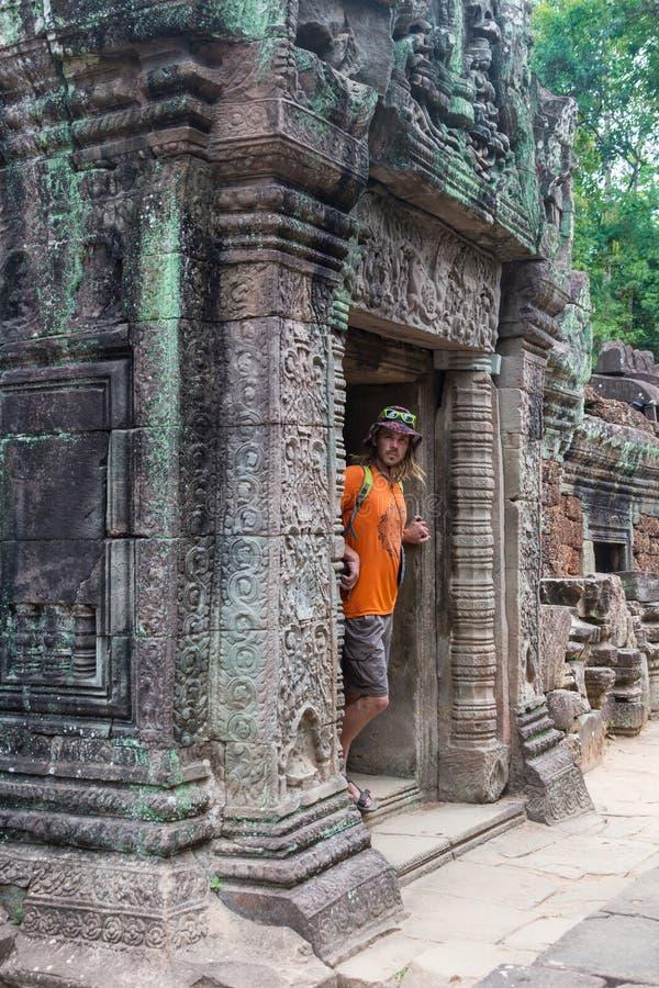 Viajero joven que lleva un sombrero con la mochila y el trípode - en Angkor Wat foto de archivo libre de regalías