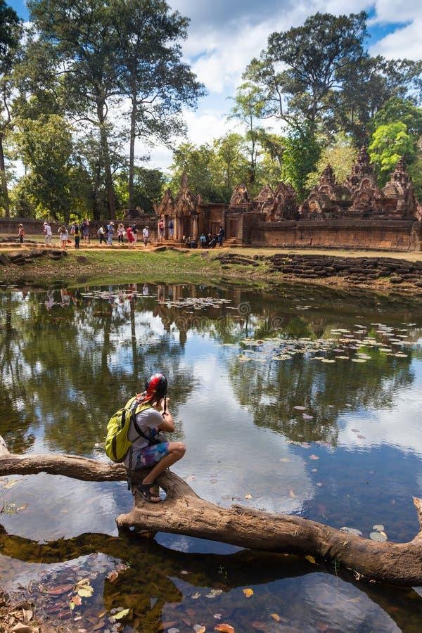 Viajero joven que lleva un sombrero con la mochila y el trípode - en Angkor Wat imagen de archivo