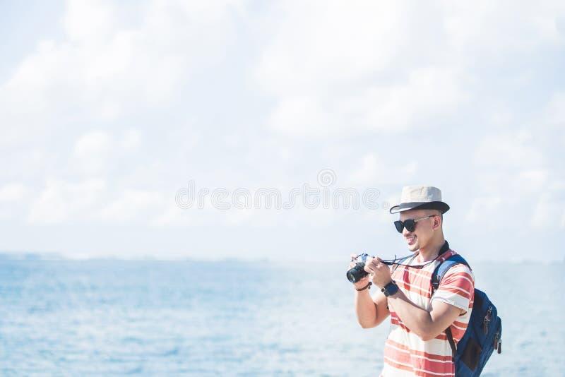 Viajero joven que toma la foto usando cámara del vintage imagenes de archivo