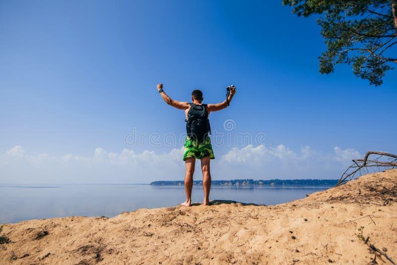 Viajero masculino con sus manos para arriba en el top con la mochila y una cámara sobre el agua foto de archivo