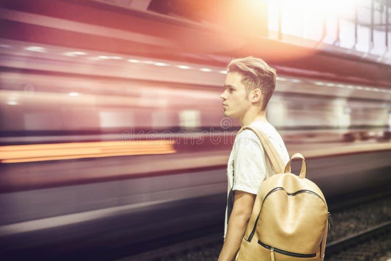 Viajero masculino joven en la estación, con apresurar borroso del tren imagen de archivo libre de regalías