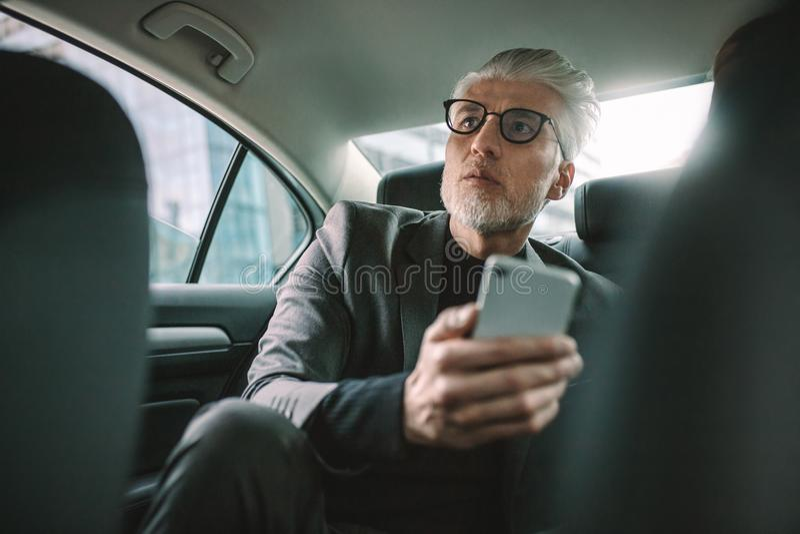 Viajero masculino maduro que viaja por un taxi imagenes de archivo