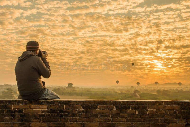 Viajero masculino que fotografía los templos en Bagan Myanmar Asia en la salida del sol imágenes de archivo libres de regalías
