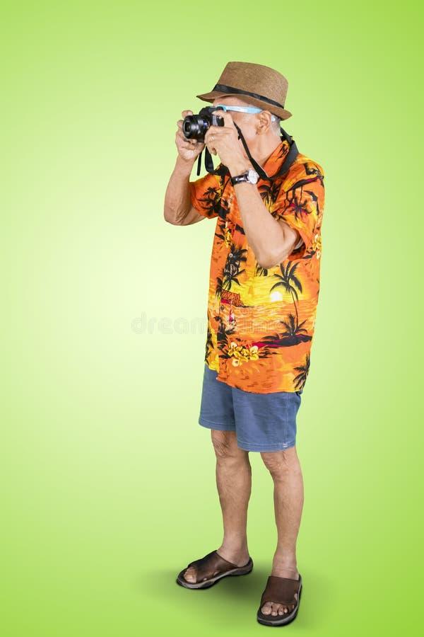 Viajero mayor que toma la foto con una cámara en estudio fotografía de archivo libre de regalías