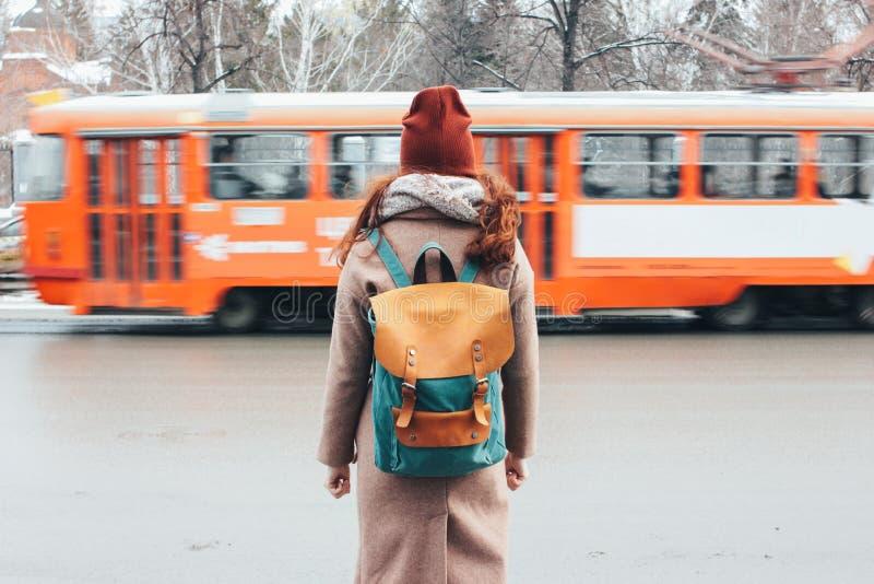 Viajero principal rojo rizado de la muchacha de la mujer joven con la mochila delante de la tranvía en la calle de la ciudad fotografía de archivo libre de regalías
