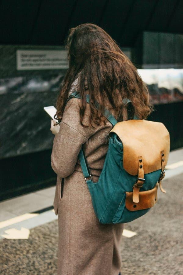 Viajero principal rojo rizado de la muchacha de la mujer joven con la mochila usando móvil en subterráneo imagenes de archivo