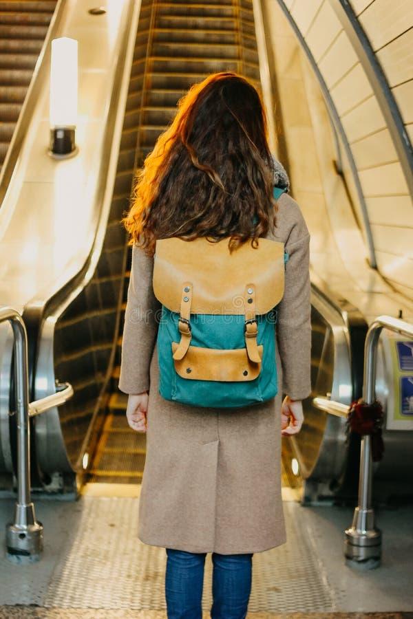 Viajero principal rojo rizado de la muchacha de la mujer joven con la mochila y mapa en la estación de metro delante de la escale fotos de archivo