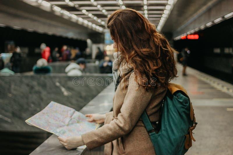 Viajero principal rojo rizado de la muchacha de la mujer joven con la mochila y mapa en subterráneo fotos de archivo libres de regalías