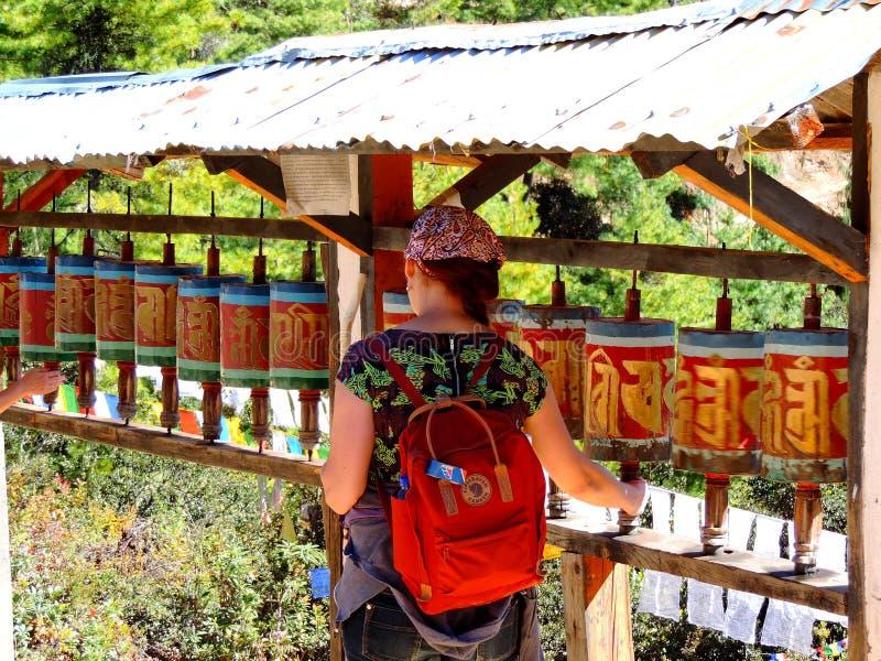 Viajero que da vuelta a la rueda religiosa en la manera a Paro Taktsang de Bhután imagenes de archivo