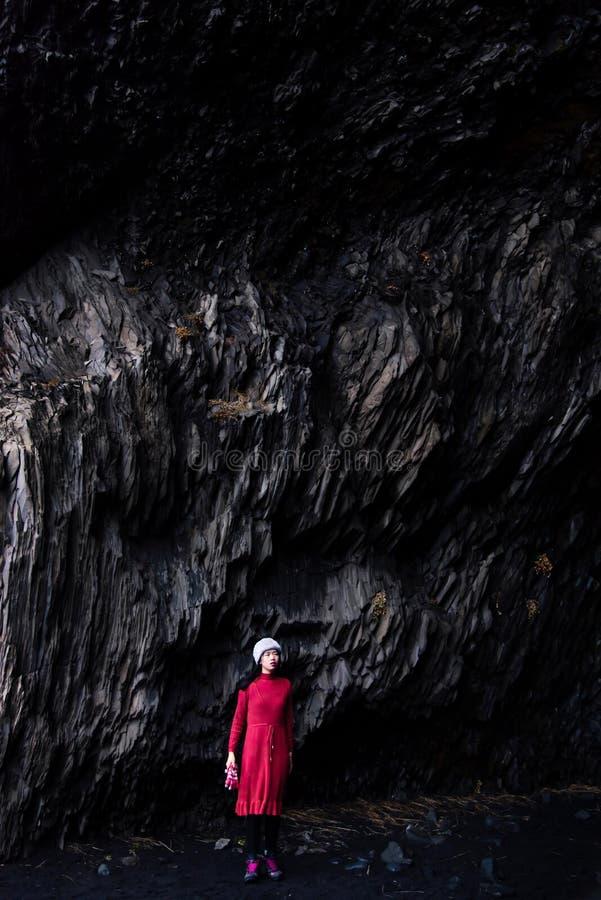 Viajero que explora la playa negra de Reynisfjara de la arena en Islandia foto de archivo