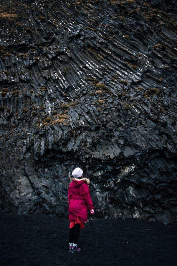 Viajero que explora la playa negra de Reynisfjara de la arena en Islandia fotografía de archivo libre de regalías