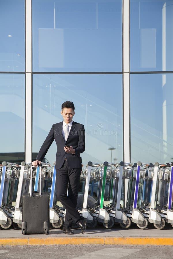 Viajero que mira el teléfono móvil al lado de la fila de los carros del equipaje fotos de archivo