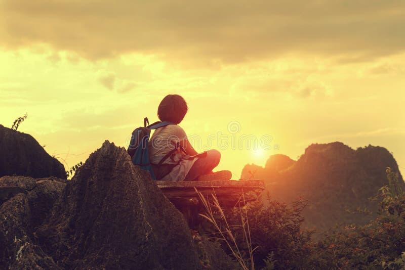 viajero que se sienta en la montaña superior con la mirada de puesta del sol foto de archivo libre de regalías