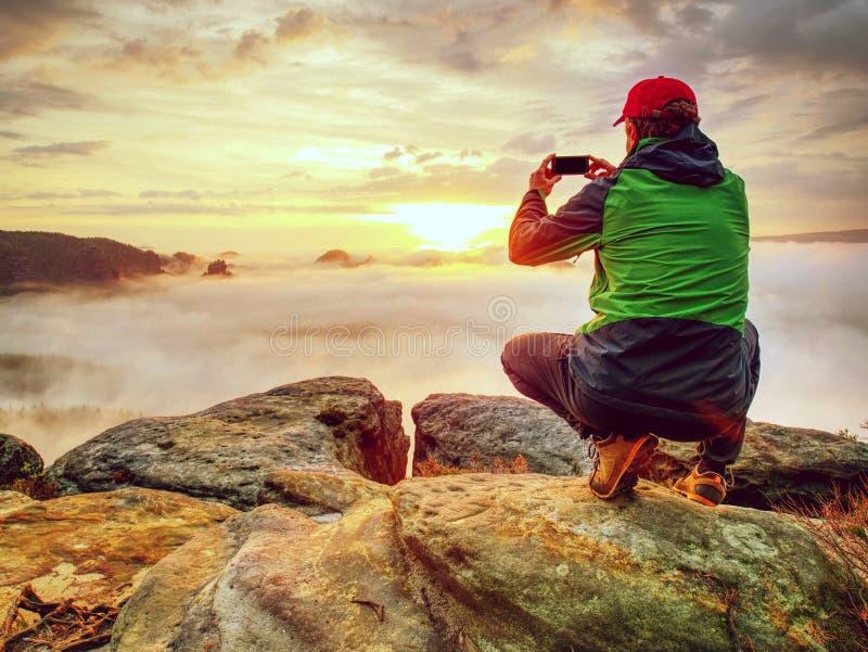 Viajero que toma las fotos móviles de las vacaciones de la puesta del sol hermosa en naturaleza del otoño fotos de archivo libres de regalías