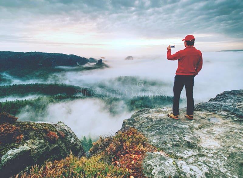 Viajero que toma las fotos móviles de las vacaciones de la puesta del sol hermosa en naturaleza del otoño imagen de archivo
