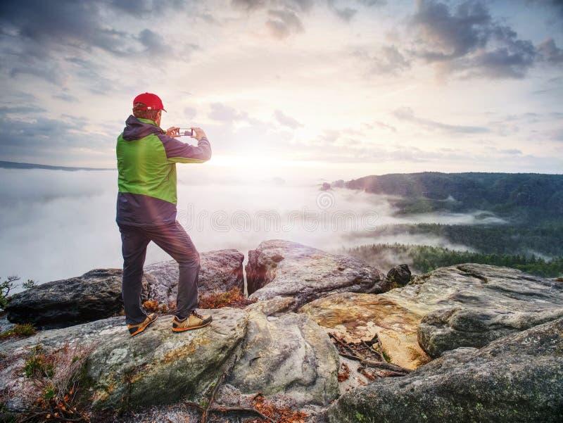 Viajero que toma las fotos móviles de las vacaciones de la puesta del sol hermosa en naturaleza del otoño fotografía de archivo libre de regalías