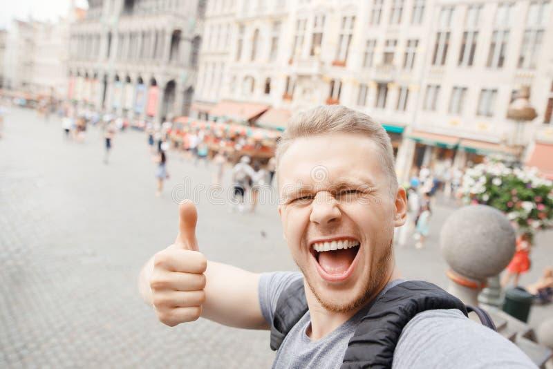 Viajero rubio barbudo joven de la sonrisa del individuo a Europa con la mochila que toma el selfie en lugar magnífico y que muest imagen de archivo libre de regalías