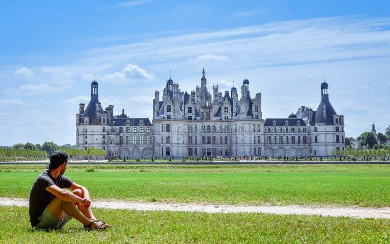 Viajero solo auténtico en un día soleado que mira el castillo de Chambord Hombre que se sienta en la hierba Francia el 7 de julio imagenes de archivo