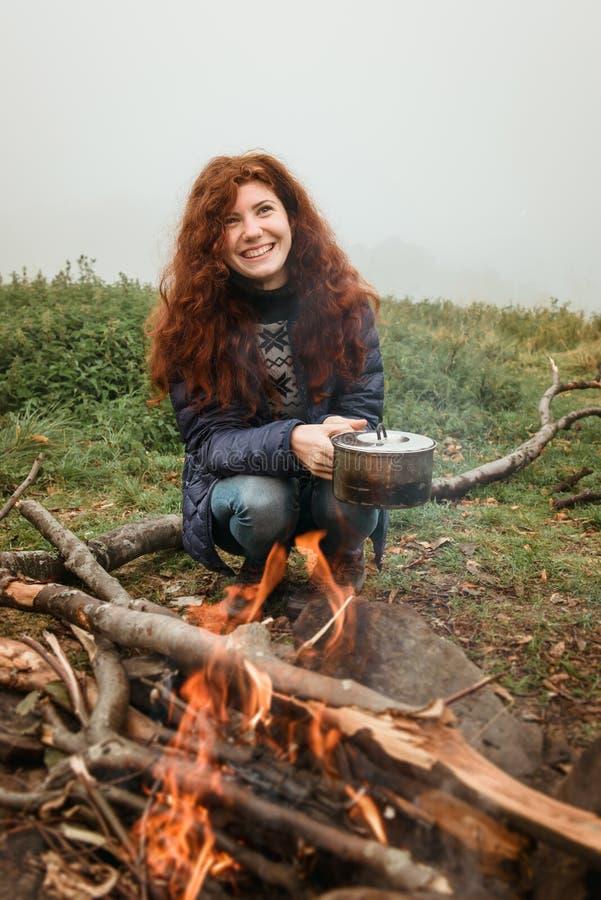Viajero sonriente que cocina la comida en el fuego al aire libre fotografía de archivo libre de regalías
