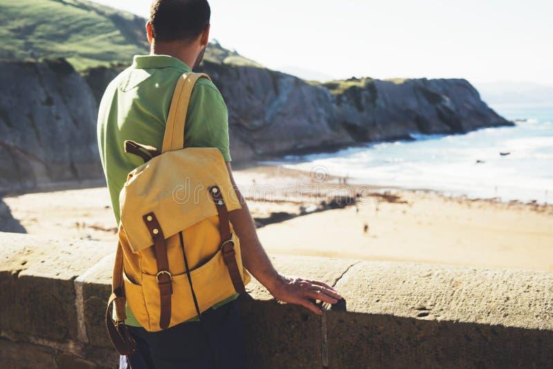 Viajero turístico con la situación amarilla de la mochila en el top verde en la montaña, opinión del caminante de la parte po fotografía de archivo