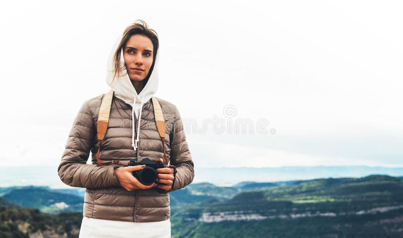 Viajero turístico que se coloca en el top del verde en la montaña que se sostiene en cámara digital de la foto de las manos, cami fotos de archivo