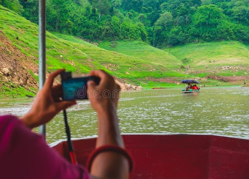 Viajero, usando la cámara para la foto de la toma con feliz El sentarse en el barco imágenes de archivo libres de regalías