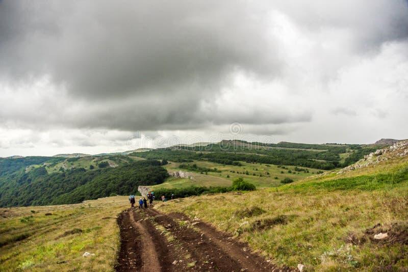 Viajeros anónimos que caminan en terreno montañoso imágenes de archivo libres de regalías