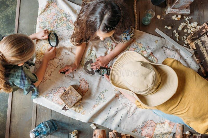 Viajeros de los niños que se sientan junto en el pórtico con el mapa fotos de archivo libres de regalías