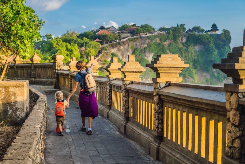 Viajeros del papá y del hijo en el templo de Pura Luhur Uluwatu, Bali, Indonesia Paisaje asombroso - acantilado con el cielo azul foto de archivo