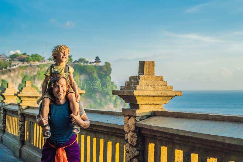 Viajeros del papá y del hijo en el templo de Pura Luhur Uluwatu, Bali, Indonesia Paisaje asombroso - acantilado con el cielo azul fotografía de archivo