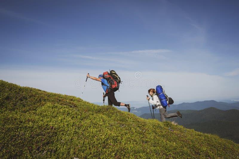 Viajeros divertidos, amigos que suben en el rastro de montaña imagenes de archivo
