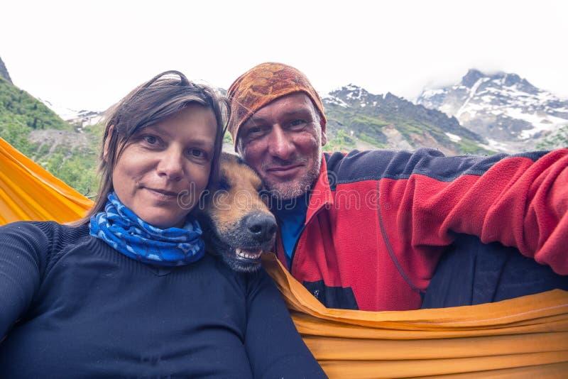 Viajeros divertidos con el perro sonriente grande, tomando el selfie en el soporte imagen de archivo libre de regalías