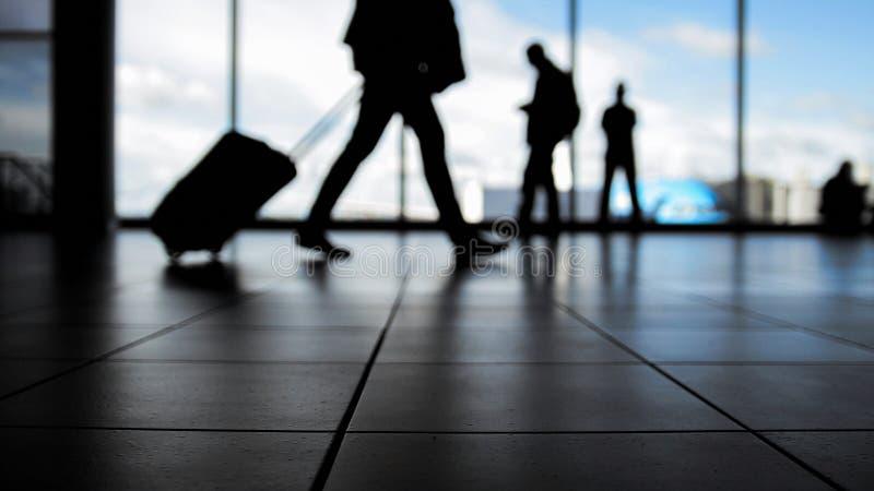 Viajeros en aeropuerto que caminan a las salidas por la escalera móvil delante de la ventana, silueta fotos de archivo