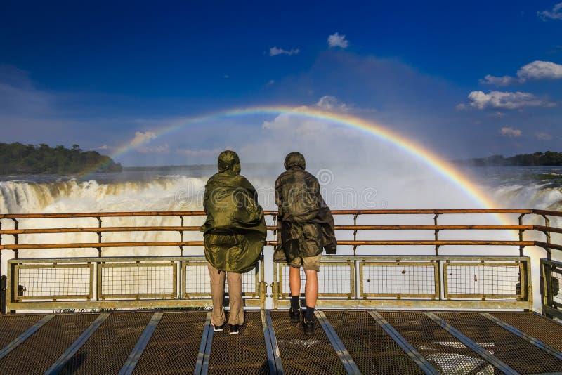 Viajeros en las cataratas del Iguazú Vista del arco iris y de una cascada imagen de archivo libre de regalías