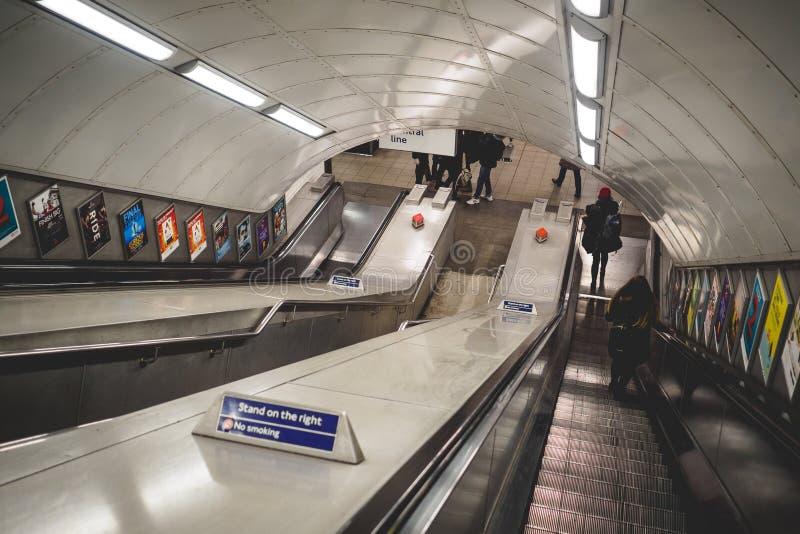 Viajeros en una escalera móvil en una estación del metro en Londres Reino Unido En junio de 2017 imagen de archivo libre de regalías