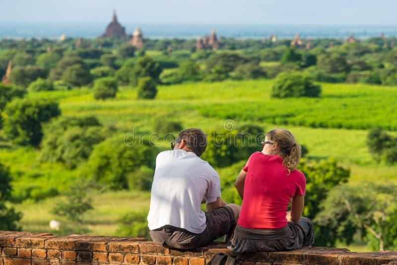 Viajeros europeos que se sientan en las pagodas que esperan la puesta del sol, Bagan fotos de archivo