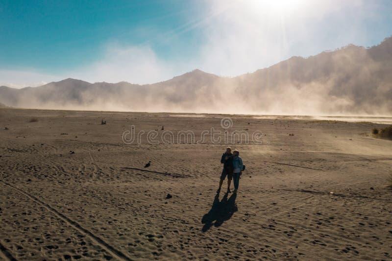 Viajeros felices de los pares que se colocan en un desierto polvoriento volcánico cerca del soporte hermoso Bromo en Java Orienta fotos de archivo