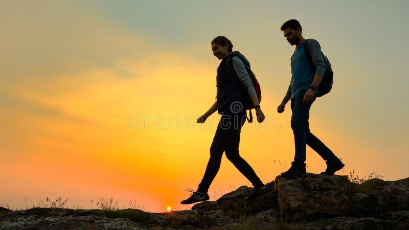 Viajeros felices jovenes que caminan con las mochilas en Rocky Trail en la puesta del sol del verano Concepto del viaje y de la a foto de archivo libre de regalías