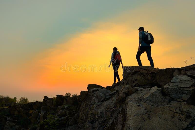 Viajeros felices jovenes que caminan con las mochilas en Rocky Trail en la puesta del sol del verano Concepto del viaje y de la a imagen de archivo