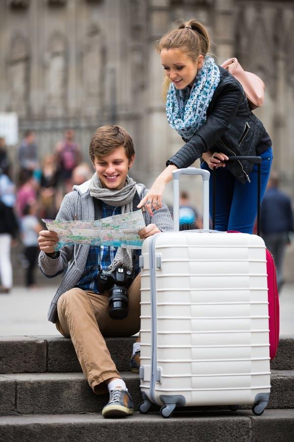 Viajeros jovenes con el mapa de la ciudad en la calle fotos de archivo libres de regalías