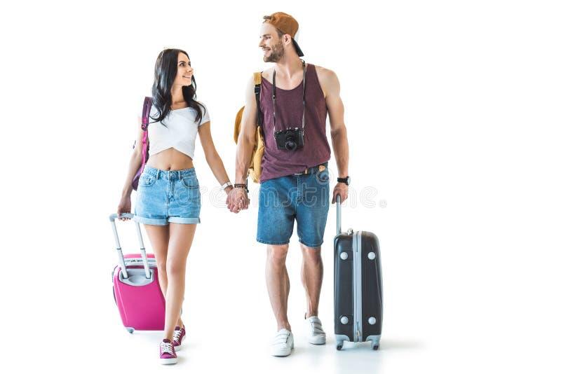 viajeros jovenes con los bolsos del viaje que llevan a cabo las manos y que miran uno a fotos de archivo libres de regalías