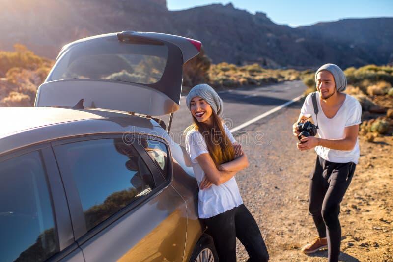 Viajeros jovenes de los pares que se divierten cerca del coche foto de archivo libre de regalías