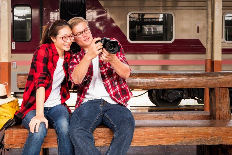 Viajeros jovenes felicesde los pares junto de vacaciones que toman una foto en la estación de tren, concepto del viaje, concepto imagen de archivo libre de regalías