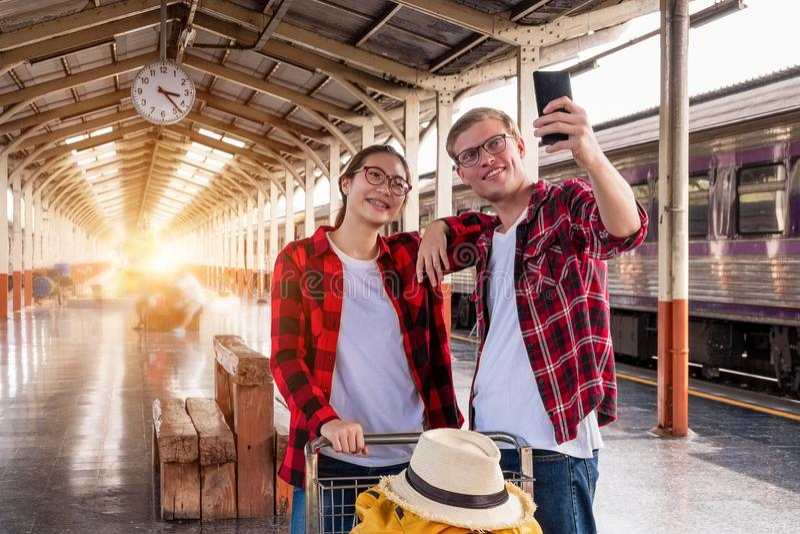 Viajeros jovenes felicesdel couplejunto de vacaciones que toman un selfie en el teléfono en la estación de tren, concepto del  foto de archivo