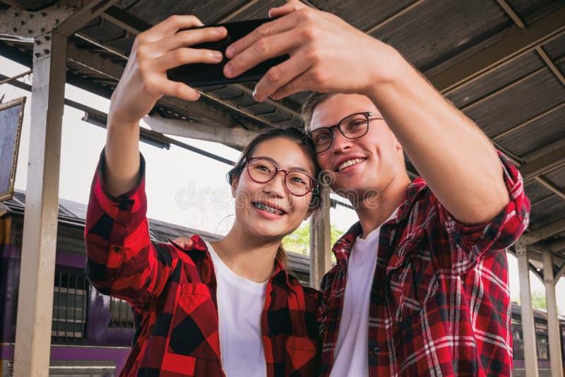 Viajeros jovenes felicesdel couplejunto de vacaciones que toman un selfie en el teléfono en la estación de tren, concepto del  foto de archivo libre de regalías