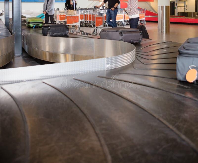Viajeros que esperan equipaje de la banda transportadora en el aeropuerto foto de archivo