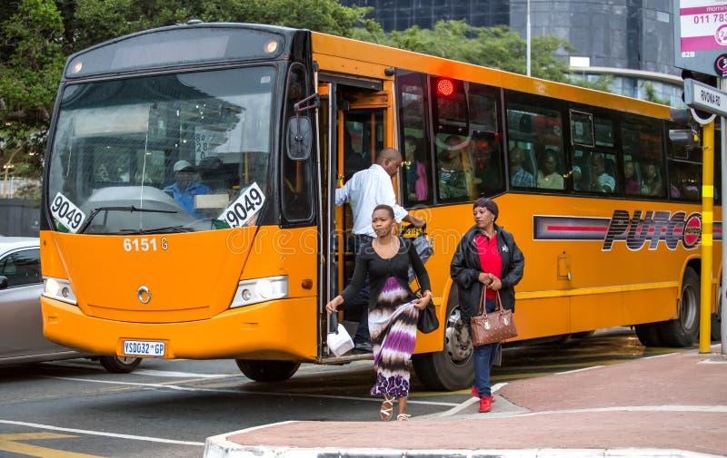 Viajeros que suben fuera del autobús en centro de ciudad fotografía de archivo